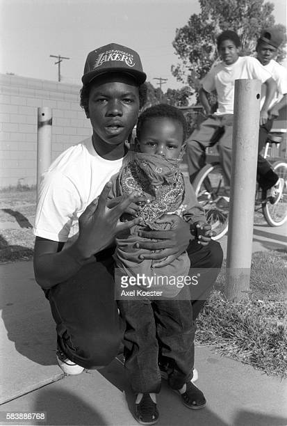 A Grape Street Crip teenager poses with his little brother The Grape Street Watts Crips are a mostly African American street gang based in the Jordan...