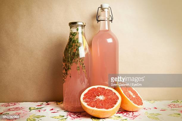Grapefruit And Juice On Table Against Wall