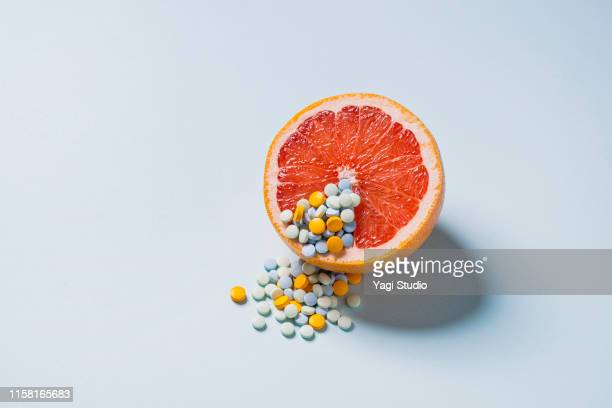 grapefruit and medicine - birth control pill stock pictures, royalty-free photos & images