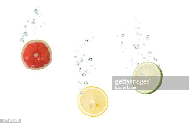 grapefruit, lemon, lime in water with air bubbles - grapefruit red stock pictures, royalty-free photos & images