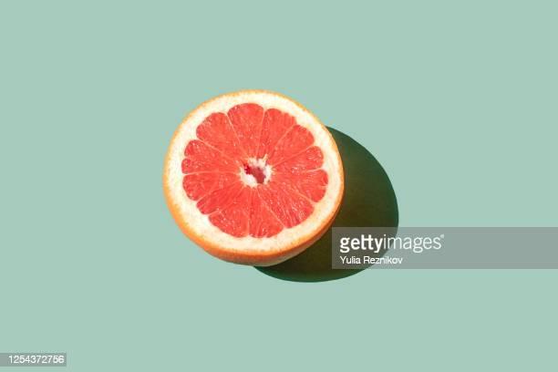 grapefruit on the green background - obst stock-fotos und bilder