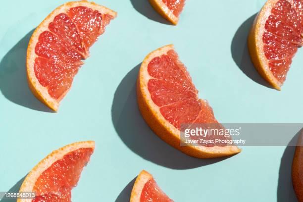 grapefruit slices on turquoise background - comida e bebida imagens e fotografias de stock
