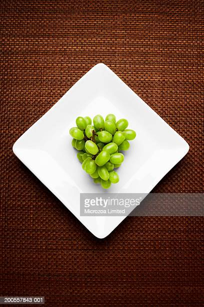 grapes on plate, overhead view - microzoa stockfoto's en -beelden