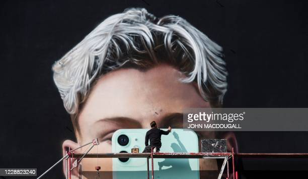 Graphic artist paints a mural ad for smartphone manufacturer Apple, in Berlin on October 1, 2020.
