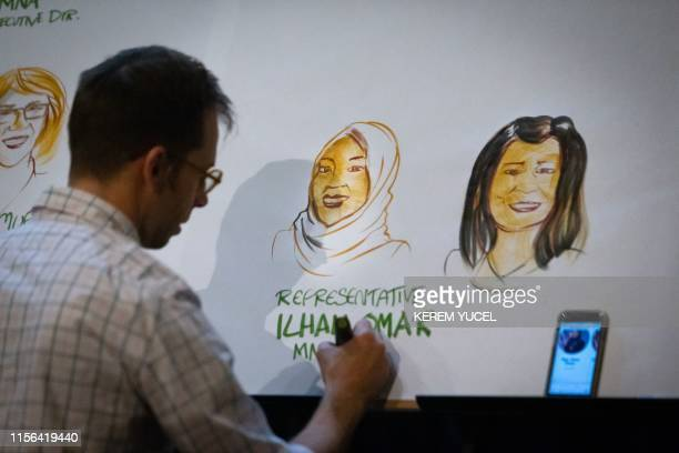 Graphic artist Timothy Fosu draws the portraits of the panelists during a Medicare for All town hall meeting held by US Representative Ilhan Omar at...