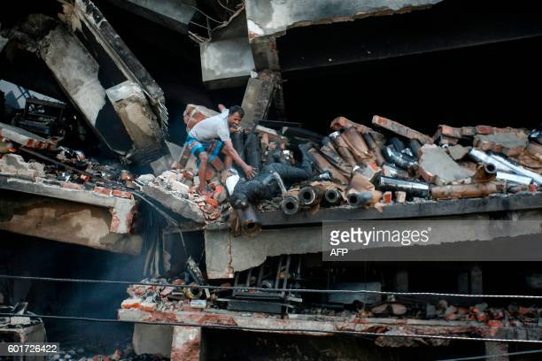 Graphic content / A Bangladeshi volunteer tries to recover a victim's body after a fire at a factory in Tongi the key Bangladeshi garment...