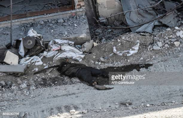 Graphic content / A body lies on a street on the western frontline in the Syrian city of Raqa on October 8 2017 Syrian Democratic Forces Syrian...