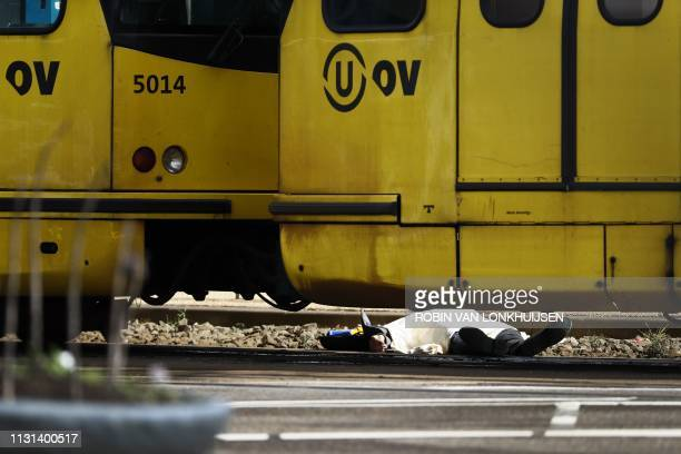 Graphic content / A body lying on the ground is covered near a tram at the 24 Oktoberplace in Utrecht on March 18 2019 where a shooting took place A...