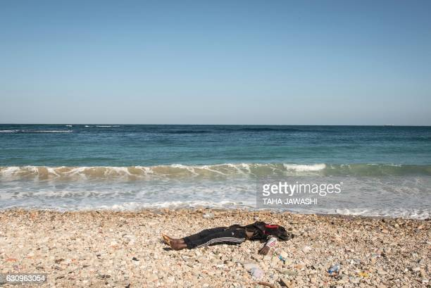 Graphic content / A body of a drowned immigrant is seen after it washed ashore in the Andalus district of the capital Tripoli on January 4 2017 After...