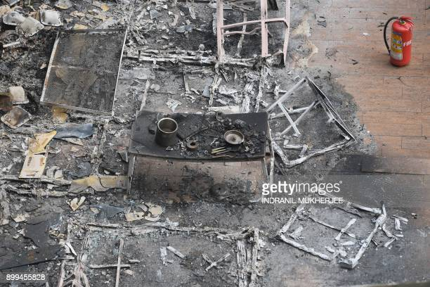 Graphic content / A burnt dining table is seen among the charred remains of a restobar where a rooftop party was being held in Mumbai early on...