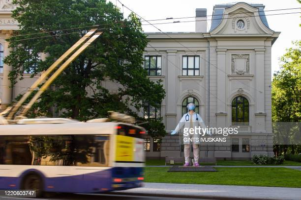 Graphic content / A bus drives past a 6 meters high statue of a female doctor by Latvian artist Aigars Bikse called Medics to the World which stands...