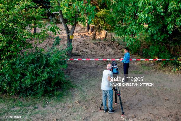 Graphic content / A camera team stands behind a police cordon to film the site after the police finished a two-day search in a garden allotment in...