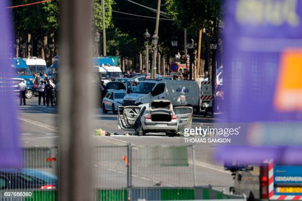 Graphic content / A car with all doors and trunk opened is pictured in a Police sealed off area of the ChampsElysees avenue in Paris on June 19 after...