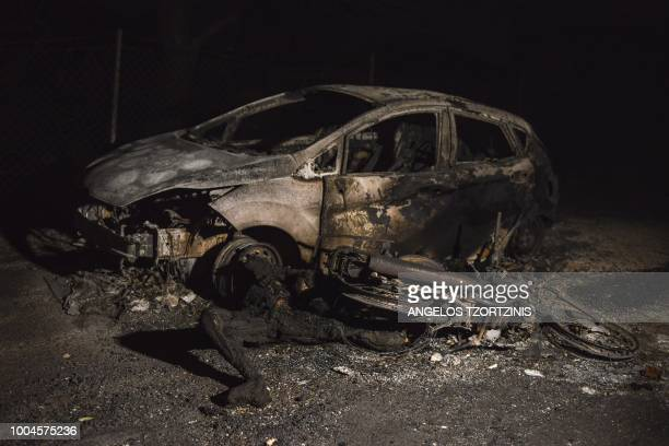 Graphic content / A charred body lies next to a car during wildfires in the village of Mati near Athens on July 23 2018 Raging wildfires killed 60...