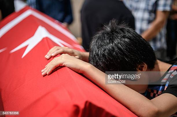 Graphic content / A child leans on the coffin of his uncle suicide attack victim Hamidullah Safar on June 30 2016 in Istanbul during his funeral two...