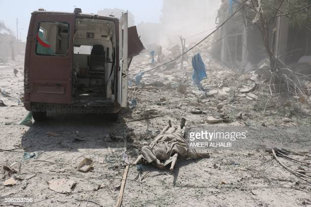 Graphic content / A corpse lies behind a damaged ambulance in the Maadi district of eastern Aleppo after regime aircrafts reportedly dropped...