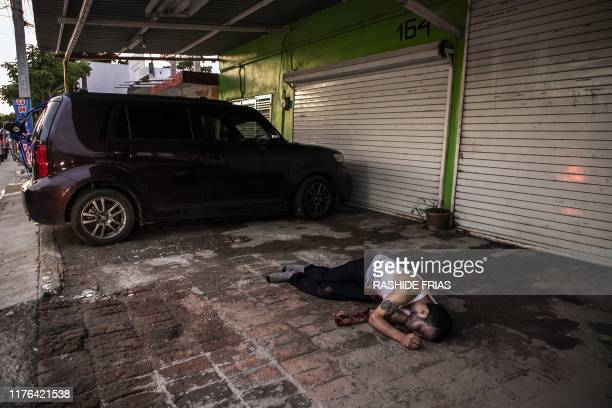 Graphic content / A corpse lies in a street of Culiacan state of Sinaloa Mexico on October 17 after heavily armed gunmen in fourbyfour trucks fought...