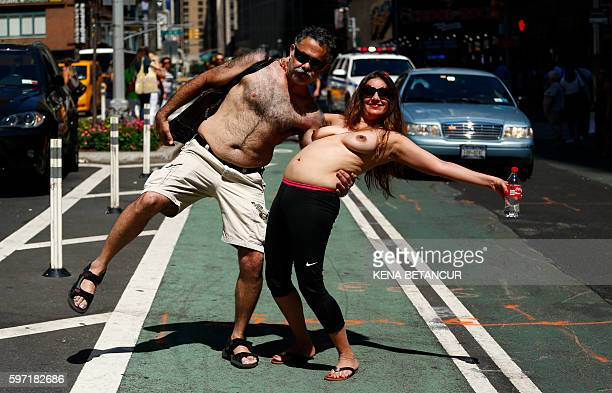 Graphic content / A couple pose as they take part in the GoTopless Pride Parade on August 28 2016 in New York Women around the US are going topless...