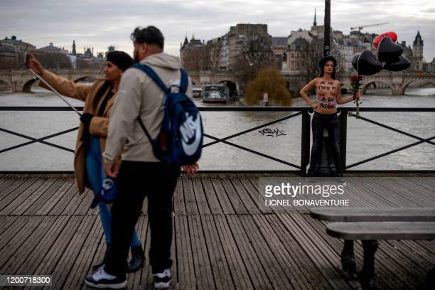 Graphic content / A couple take a selfie picture as a member of the feminist movement Femen is chained on the pont des Arts in Paris on February 14...