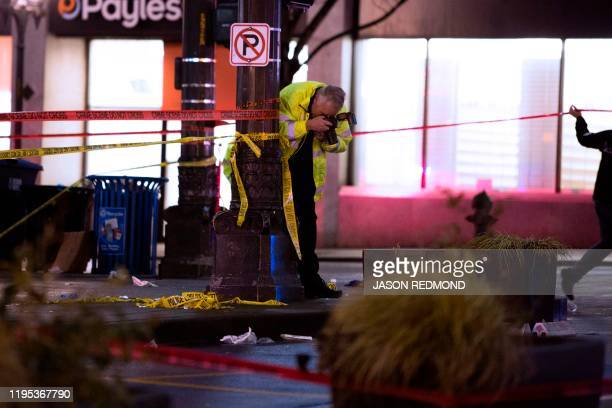 Graphic content / A crime scene investigator photographs the scene of a shooting that left one person dead and seven injured, including a child, in...