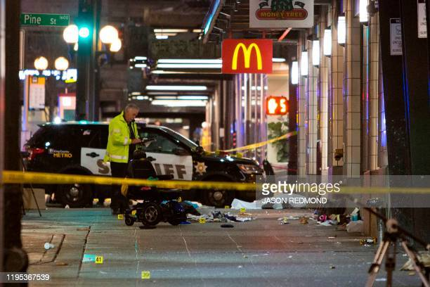 Graphic content / A crime-scene investigator inspects the scene of a shooting that left one person dead and seven injured, including a child, in...