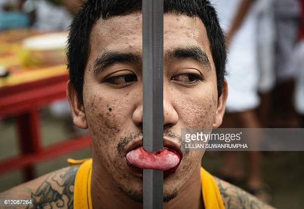 Graphic content / A devotee of the Nine Emperor Gods is seen with a sword pierced through his tongue during the annual Phuket Vegetarian Festival in...