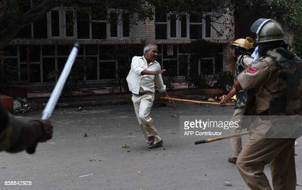 Graphic content / A follower of Indian religious leader Gurmeet Ram Rahim Singh is hit with a stick during clashes between the controversial guru's...