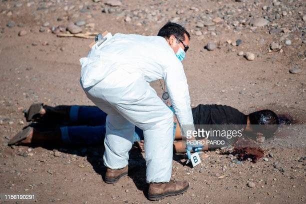 Graphic content / A forensic officer works at the crime scene next to the body of a man killed during a shooting in Culiacan Sinaloa Mexico on July...