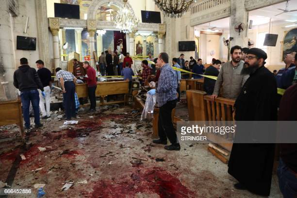 Graphic content / A general view shows people looking at the aftermath following a bomb blast which struck worshippers gathering to celebrate Palm...