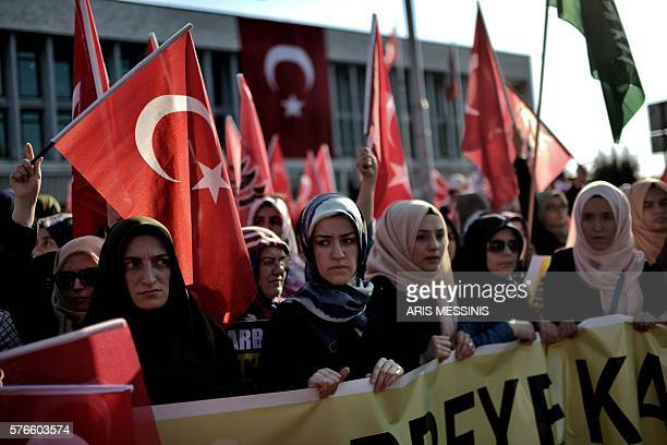 Graphic content / A group of women holds a banner as ProErdogan protesters wave Turkish flags during a demonstration in Istanbul in support the...