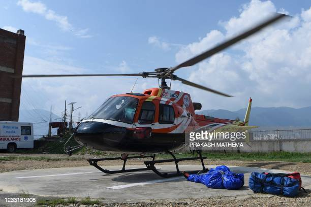 Graphic content / A helicopter lifts off after transporting the body of American mountaineer Puwei Liu as he was recovered from Mount Everest, in...
