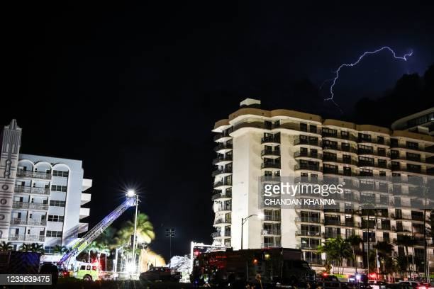 Graphic content / A lightning strikes above the Champlain Towers South as Search and Rescue personnel work after the partial collapse of the...