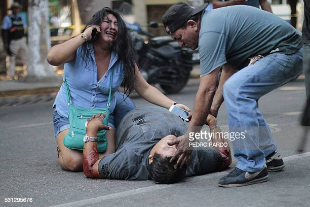 Graphic content / A man and a woman help a relative shot in the tourist area of Acapulco Guerrero State Mexico on May 13 2016 / AFP / PEDRO PARDO
