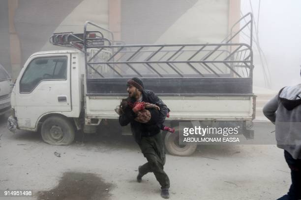 Graphic content / A man carries a child as he flees from reported Syrian air force strikes that hit the rebelheld town of Saqba in the besieged...