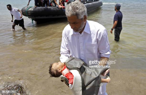 Graphic content / A man carries the body of a baby as migrants who survived the sinking of an inflatable dinghy boat off of the coast of Libya are...