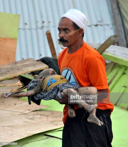 Graphic content / A man carries the body of a child after an earthquake and tsunami hit Palu on Sulawesi island on September 29 2018 Rescuers...