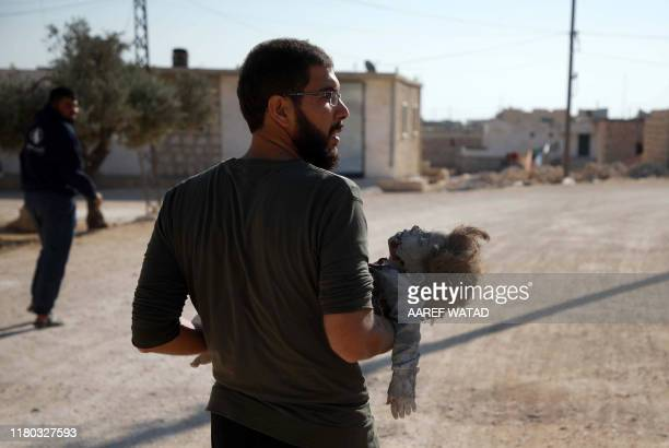 Graphic content / A man carries the body of a girl who was killed in a reported air strike in the Syrian village of alSahharah in the countryside...