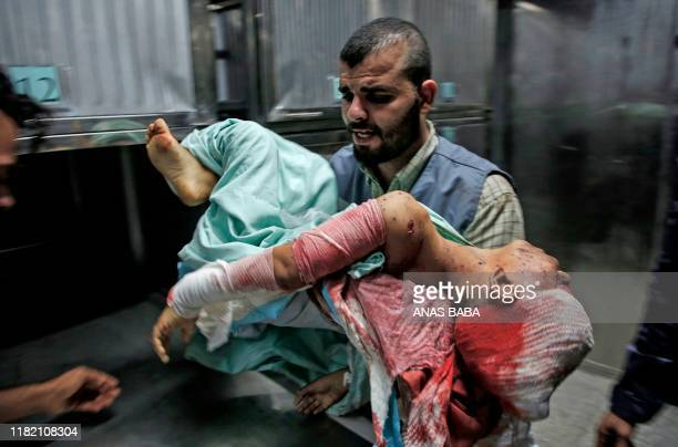 Graphic content / A man carries the body of Amir Ayad, a Palestinian boy who was killed in an Israeli strike on November 13 at the mortuary of Gaza...