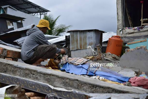 Graphic content / A man grieves over the body of a victim in Mamuju city on January 15 after a 6.2-magnitude earthquake rocked Indonesia's Sulawesi...