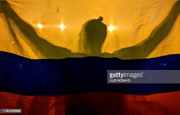 Graphic content / A man holds a national flag during a 'cacerolazo' a day after a nationwide strike by students, unions and indigenous against the...