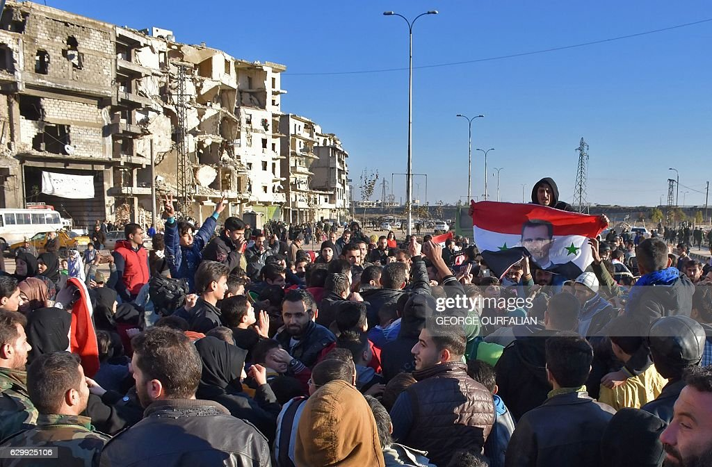 Graphic content / A man holds the Syrian flag bearing a portrait of the Syrian president as residents in a government-held area of Aleppo gather in the street during an evacuation operation of rebel fighters and their families from rebel-held neighbourhoods in Syria's northern embattled city on December 15, 2016. A convoy of ambulances and buses left rebel territory in Aleppo in the first evacuations under a deal for opposition fighters to leave the city after years of fighting. The rebel withdrawal will pave the way for President Bashar al-Assad's forces to reclaim complete control of Syria's second city, handing the regime its biggest victory in more than five years of civil war. / AFP / George OURFALIAN