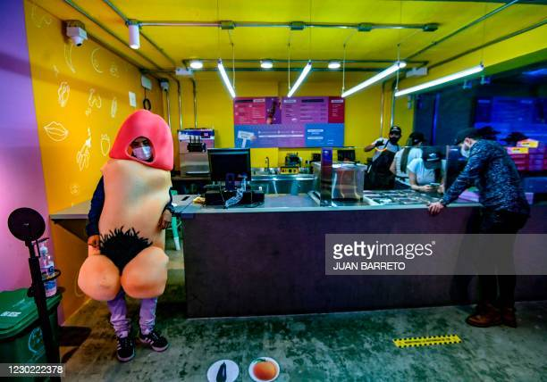 Graphic content / A man in a penis costume, leans against the counter in a sex food store in Bogota on December 19, 2020.