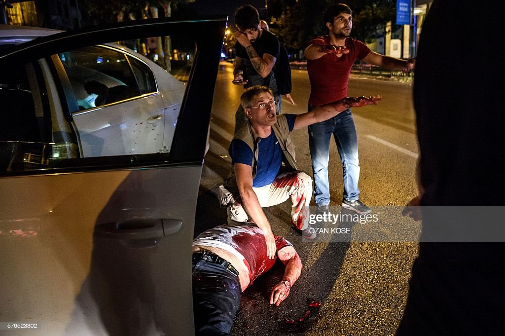 Graphic content / A man is shot in his car during clashes between Turkish solders and police near Taksim square in Istanbul on July 16, 2016. Turkish military forces on July 16 opened fire on crowds gathered in Istanbul following a coup attempt, causing casualties, an AFP photographer said. The soldiers opened fire on grounds around the first bridge across the Bosphorus dividing Europe and Asia, said the photographer, who saw wounded people being taken to ambulances. KOSE