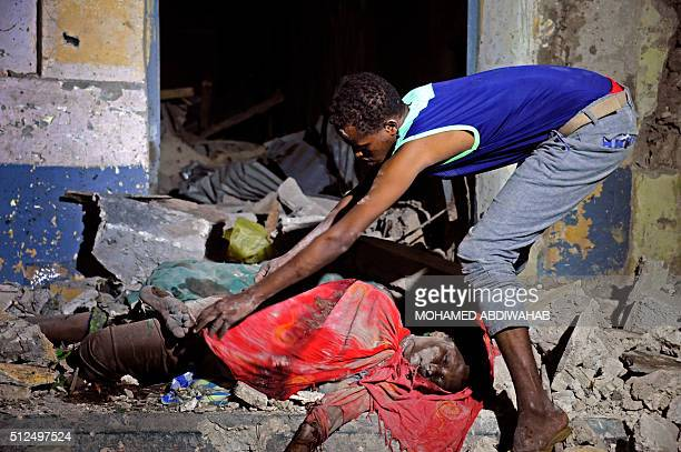 Graphic content / A man looks at the dead body of a person killed during an attack in the center of Mogadishu on February2016 Two loud explosions...