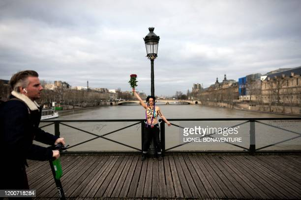 Graphic content / A man on a scooter passes as a member of the feminist movement Femen is chained on the pont des Arts in Paris on February 14 2020...