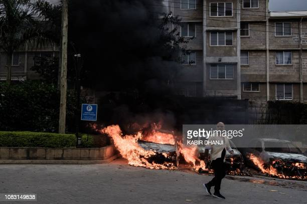 Graphic content / A man passes in front of burning cars that exploded at the entrance of DusitD2 hotel in Nairobi Kenya on January 15 after a blast...