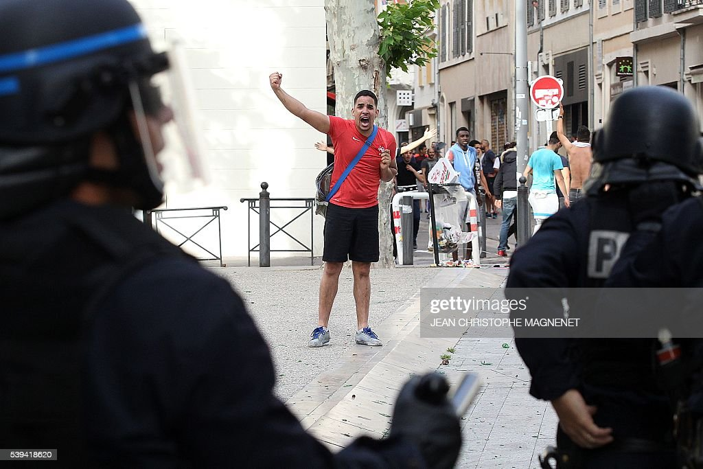 Graphic content / A man shouts to policemen during street brawls ahead of the Euro 2016 football match England vs Russia, southern France, on June 11, 2016. Football fans fought pitched battles for the third day in the French city of Marseille ahead of England's European Championship clash with Russia. Bare-chested English and Russian supporters hurled bistro chairs and bottles in the historic Vieux-Port district where the cobbled streets were littered with broken glass and debris. MAGNENET