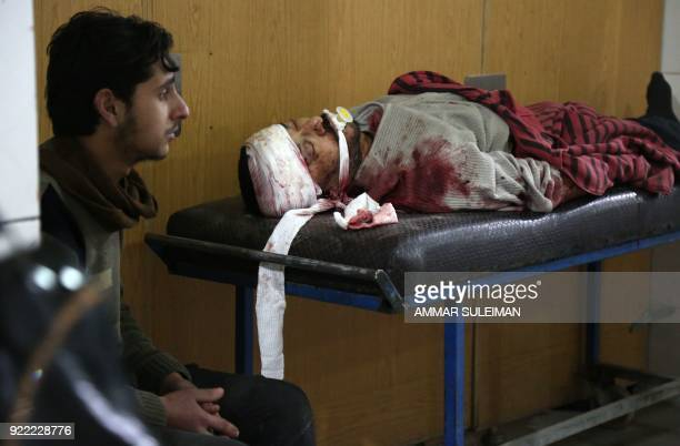 Graphic content / A man sits next to a wounded Syrian man at a makeshift hospital in Kafr Batna following Syrian government bombardments on the...