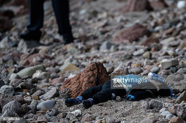 Graphic content / A man stands by the body of a migrant child washed up on a beach in Canakkale's Bademli district on January 30 2016 after at least...