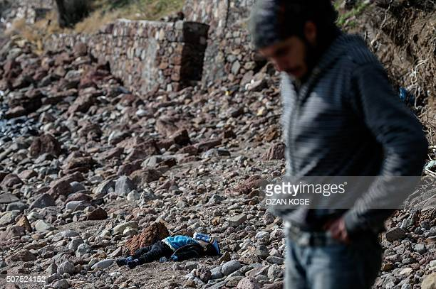 Graphic content / A man stands next to the body of a migrant child washed up on a beach in Canakkale's Bademli district on January 30 2016 after at...
